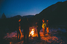 family standing around a camp fire