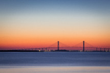 a bridge over a bay at sunset