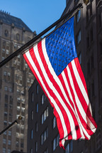American flag waving in a city