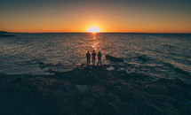 three friends watching the sun rise over the ocean