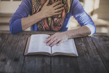 A woman reading the Bible with her hand over her heart