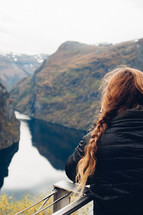 a woman with braided hair looking out at a lake in a canyon