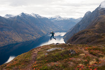 a man leaping in the air and a lake in a valley