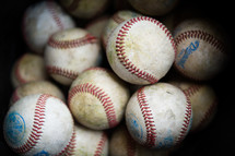 pile of worn baseballs