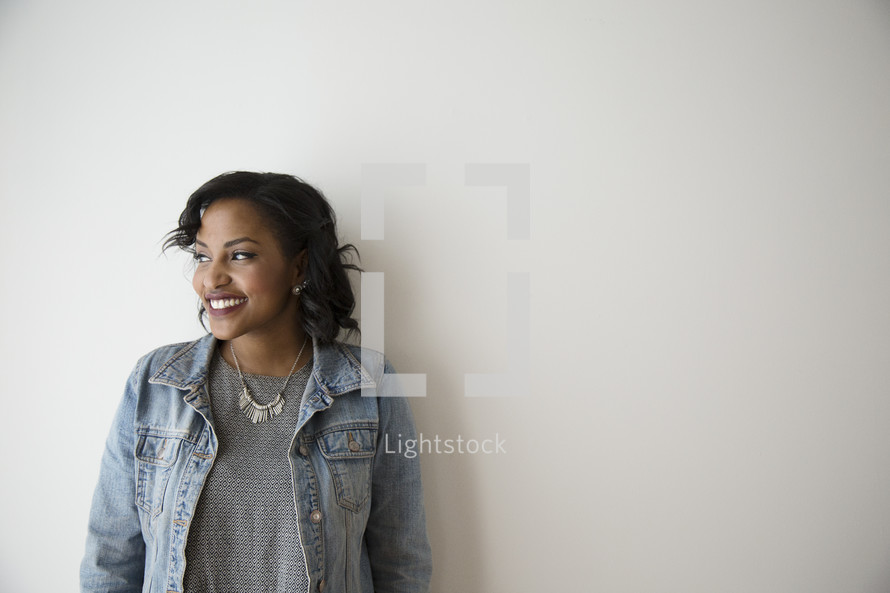 portrait of an African American leaning against a wall in a jean jacket
