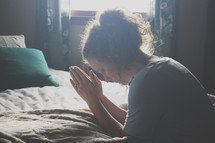 a woman praying at her bedside
