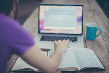 woman, open Bible, journal, computer screen, and coffee mug