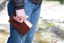 Man in jeans holding a Bible while standing outdoors.