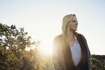 sunburst and blonde woman standing outdoors