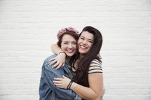 Two young women smiling and embracing in front of a white brick wall.