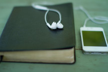 earbuds on a Bible and an iPhone