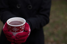 A cup of hot chocolate in a Christmas cup being held by a woman wearing red mittens.