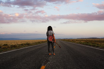 woman standing in the middle of a road with a guitar case at sunset