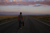 a man standing in the middle of a road with a suitcase at sunset