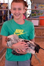 a child holding a chicken at a petting zoo
