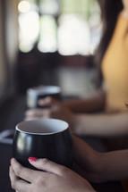 two woman holding coffee mugs
