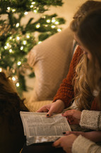 Two women reading the Bible together near a Christmas tree.