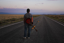 man standing in the middle of a road with a guitar at sunset