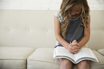 a girl child praying over an open Bible