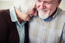 a mature couple laughing together.
