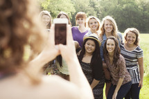 Group of young teenage women, posing for a picture being taken with a cell phone