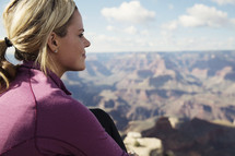 woman sitting at the edge of a canyon cliff.