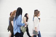women walking carrying Bibles