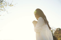 woman with praying hands outdoors under sunlight