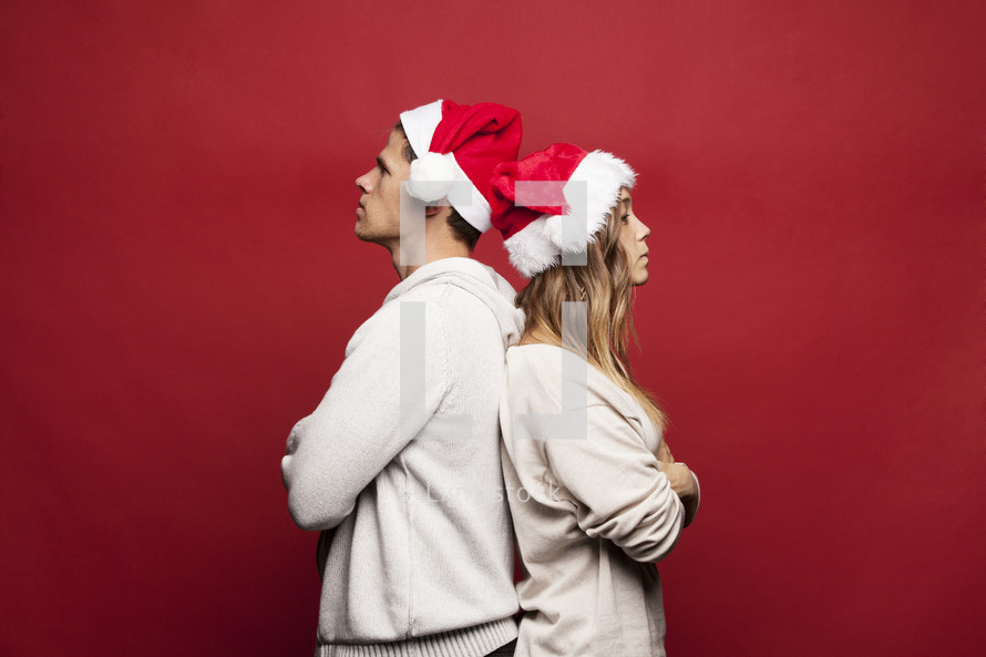 man and woman in santa hats back to back not speaking to each other