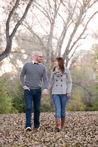 a couple walking holding hands in fall leaves