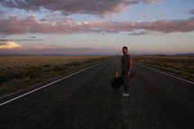 man standing in the middle of a road with a guitar case at sunset