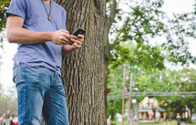 man texting standing next to a tree