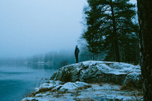 man standing on a rock by a lake shore in winter