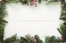 pine garland and berry border on white wood background.