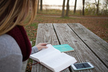 a woman sitting at a picnic table reading a Bible