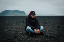 a man sitting on a black sand beach