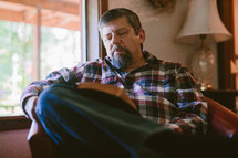 a man sitting on a couch reading a Bible