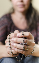 woman holding a rosary in prayer