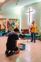 teens kneeling on the floor during a worship service