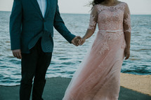 bride and groom on a beach holding hands