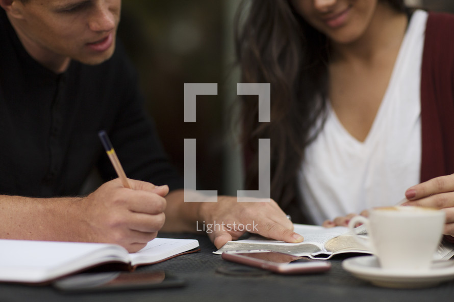 close up of a young man and young woman reading a Bible and discussing scripture together.