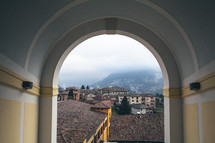 View through an archway of tile roofs, stucco buildings, and foggy mountains.