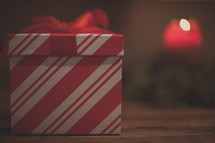A red and white gift box and candle
