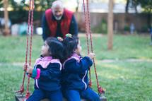 children swinging on a swing