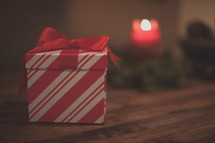 A red and white gift box and a candle on wood