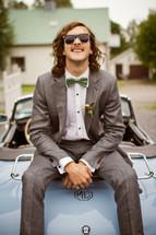 groom sitting on an vintage car
