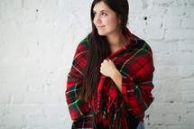 a woman wrapped in a plaid shawl