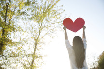 woman holding up a paper heart outdoors