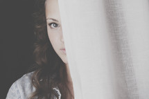 teenage girl timidly peeking from behind a curtain.