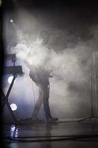 guitarist on stage under smoke